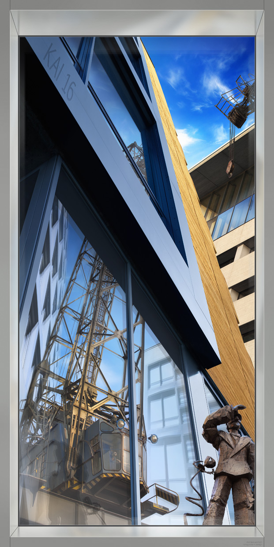 Diese hochformatige Fotokunst zeigt eine aufwendige Auftragsarbeit: eine Collage des berühmten Chipperfield-Hauses im Düsseldorfer Hafen mit surrealen Spiegelungen des denkmalgeschützten Krans und einer Bronze des Künstlers Jörg Immendorff.