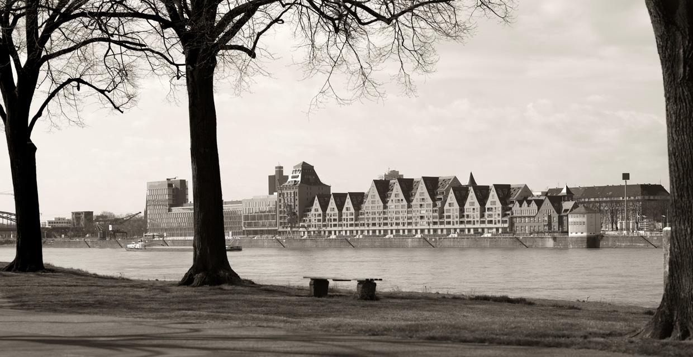 Ein Schwarz-Weiß-Foto, warm coloriert, zeigt einen Kölner Rheinabschnitt in Höhe der alten Lagergebäude, den sogenannten Siebengebirgshäusern. Es ist ein Kunstwerk hinter Acryl, beauftragt durch einen Kölner Architekten.
