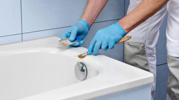 Fotografie für eine Reparatur- oder Bedienungsanleitung. Sauber beleuchtetes, professionelles Bild eines Monteurs beim Reparieren eines Schadens an einer weißen Badewanne.