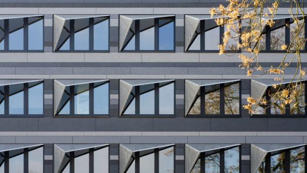 Architekturfotografie: Eine neugestaltete Fassadenansicht mit symmetrisch angeordneten Fenstern und auffälligem Sonnenschutz aus Edelstahl-Lochblechen.