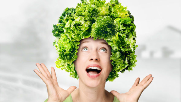 Digitales Composing: Durch besondere Fotografie und professionelle Montage und Bildbearbeitung erhält eine junge Frau eine ganz auffällige verrückte Frisur - einen riesigen Lockenkopf aus vielen sattgrünen Salaten - so fällt gesunde Ernährung in der Werbung besonders auf.